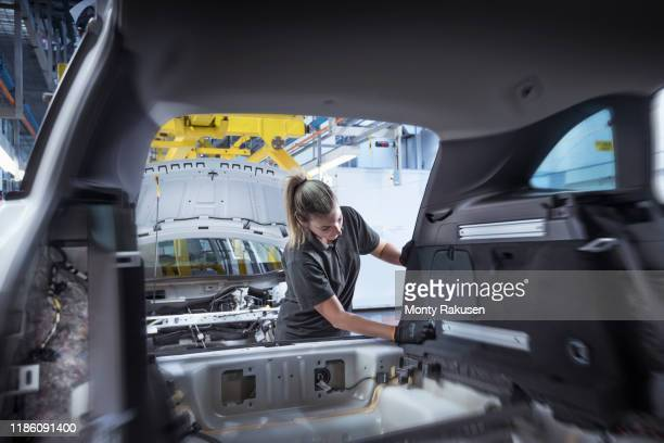 female worker assembling car interior on production line in car factory - uniform stock pictures, royalty-free photos & images