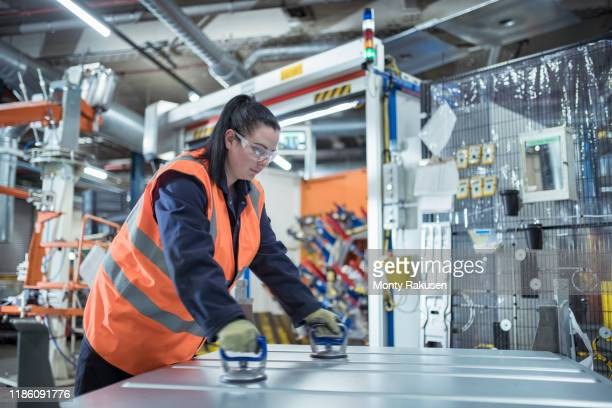 female worker assembling vehicle roofs in car factory - engineer stock pictures, royalty-free photos & images