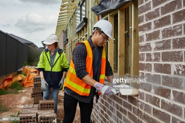 Female worker assisting bricklayer at site