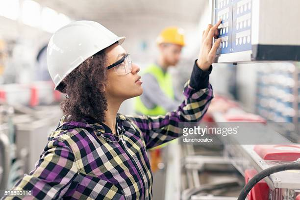Female worker at control table in the factory