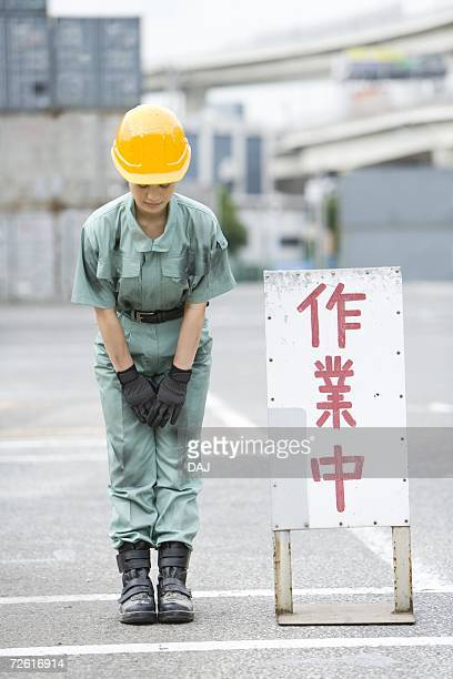 Female worker bowing, Front View, Differential Focus