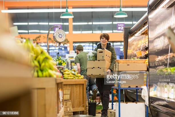 female worker carrying boxes while working at supermarket - cavan images foto e immagini stock