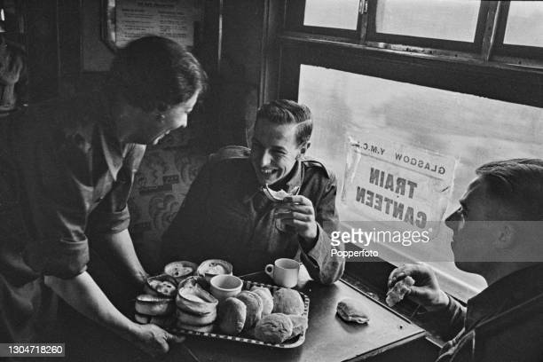 Female worker from the Young Men's Christian Association serves pies and rolls to British servicemen from their on-board canteen in a train carriage...