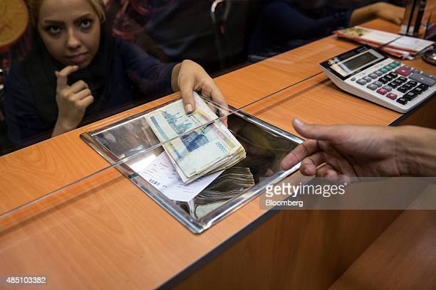 A female worker hands a customer a bundle of rial banknotes inside a foreign currency exchange at a shopping center in Tehran Iran on Saturday Aug 22...