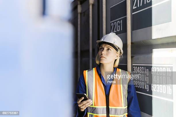 Female worker holding mobile phone in shipyard