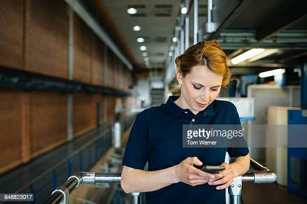 Female worker in a factory checking smart phone