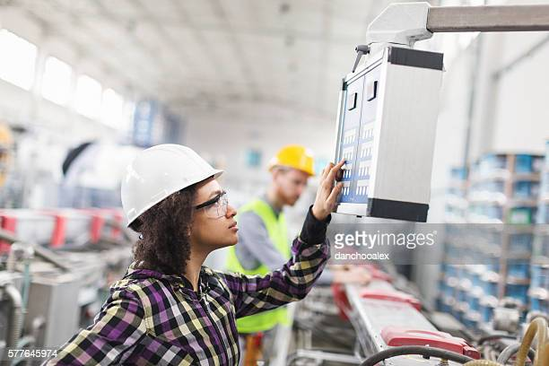 Female worker in factory using control panel for machine