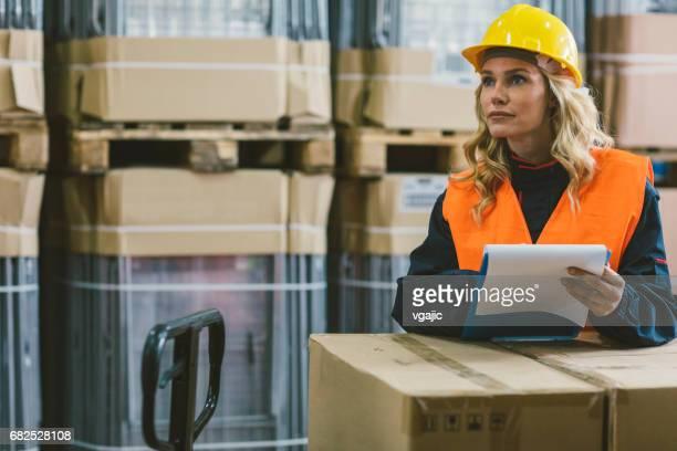 Female worker in warehouse checking merchandise