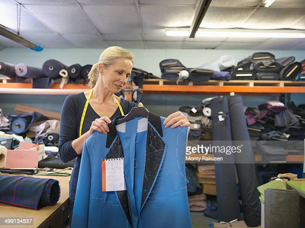 Female worker inspecting jacket in clothing factory