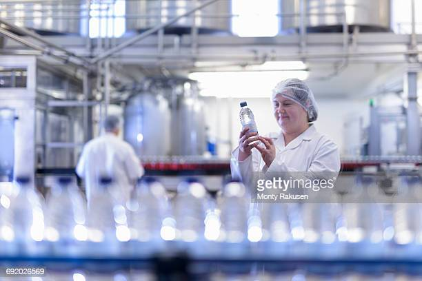 Female worker inspecting water bottle on production line in spring water factory