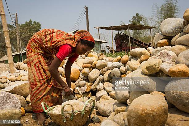A female worker is collecting stones to put those in crashing machine in a Stone Crashing Plant in Sylhet Bangladesh A huge percentage of stone is...