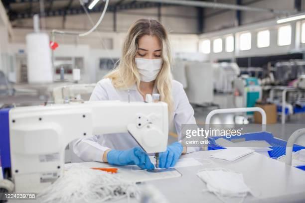 vrouwelijke arbeider die medisch masker op een naaimachine maakt - beschermend masker werkkleding stockfoto's en -beelden