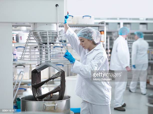female worker mixes chocolate in cake factory - chocolate factory stock photos and pictures
