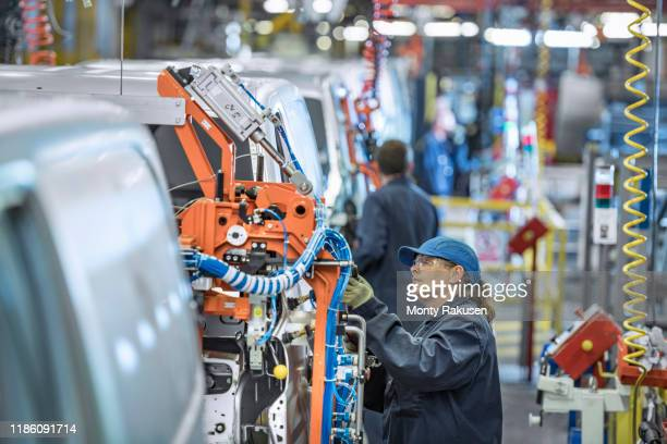 female worker on vehicle production line in car factory - place of work stock pictures, royalty-free photos & images