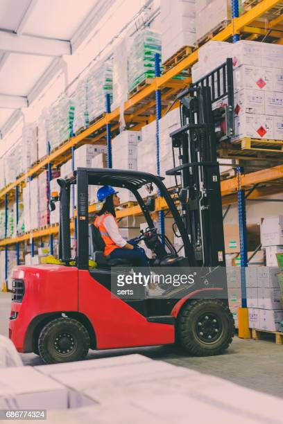 Female worker operating a forklift in warehouse