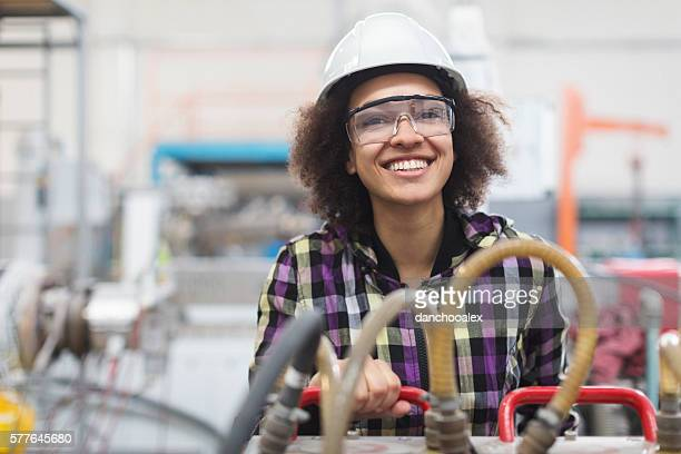 female worker operating a machine and smiling for the camera - ポリマー ストックフォトと画像