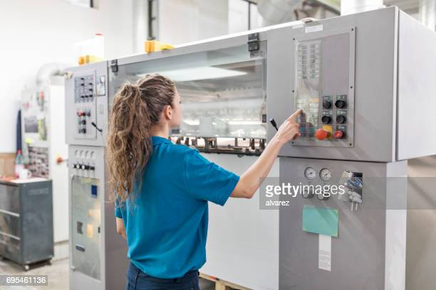 Female worker operating machine at printing plant