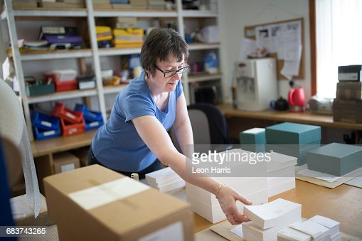 Female worker packing stacked paper in printing press workshop