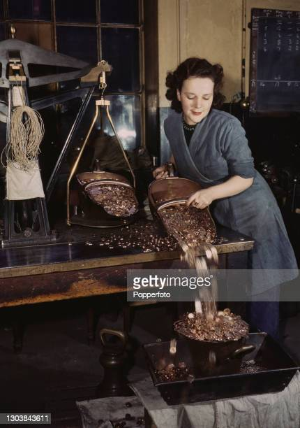 Female worker pours a hopper of decorations and medals from one weighing hopper scoop to another placed on a set of scales at the Royal Mint housed...