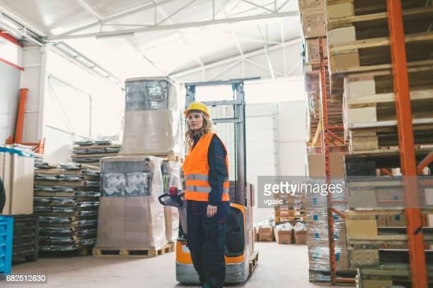Female worker pulling pallet jack in warehouse