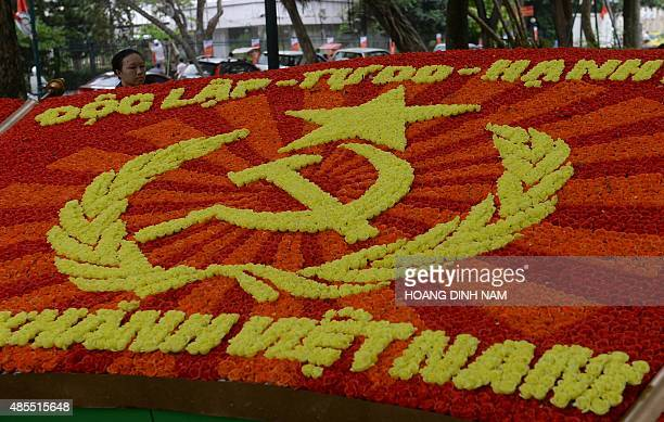 A female worker removes dead leaves on a communist display made of plastic flowers to mark the 70th anniversary of the communist Vietnam's...