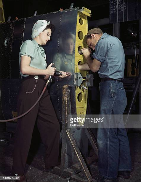 A female worker rivets the wing of a airplane at a defense factory during World War II
