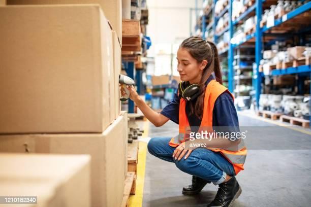 weibliche arbeiterin scannt boxen im lagerregal - fracht stock-fotos und bilder