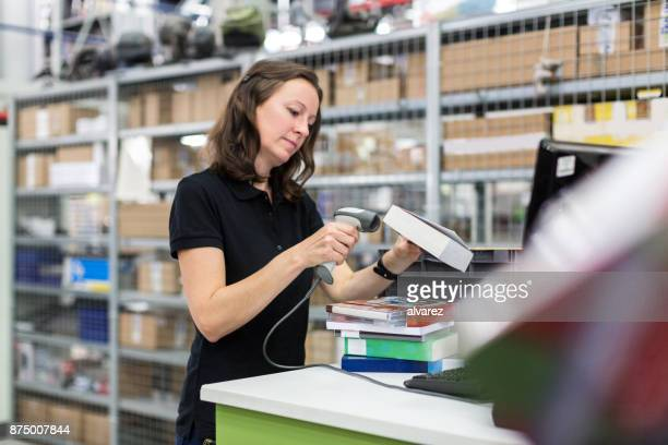 Female worker scanning package for delivery