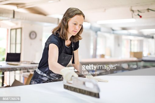 Female worker scraping paint on table
