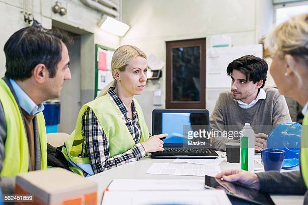 Female worker showing something on laptop to colleagues in factory