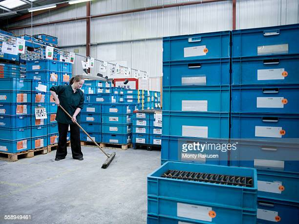 Female worker sweeping amongst stacked blue crates in factory