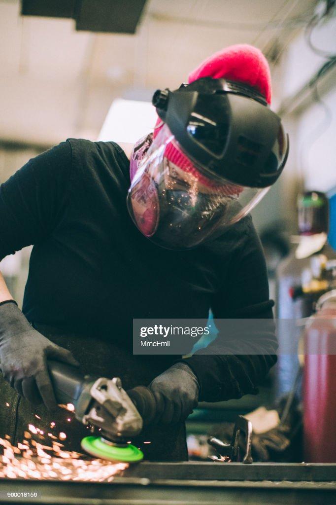 Arbeitnehmerin, die mit einem Winkelschleifer zum Schleifen : Stock-Foto