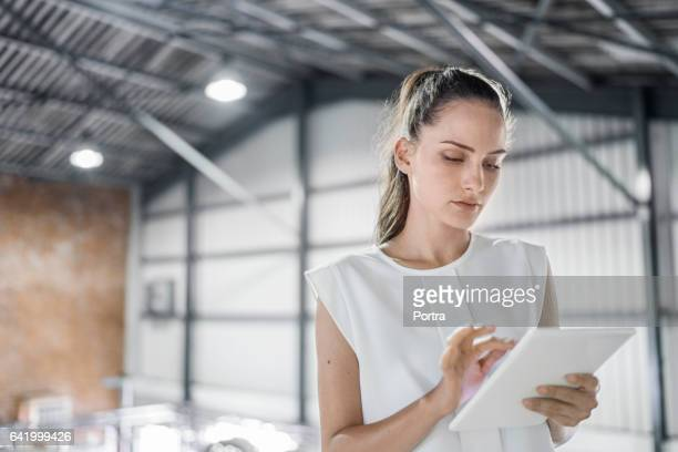 Female worker using digital tablet at brewery