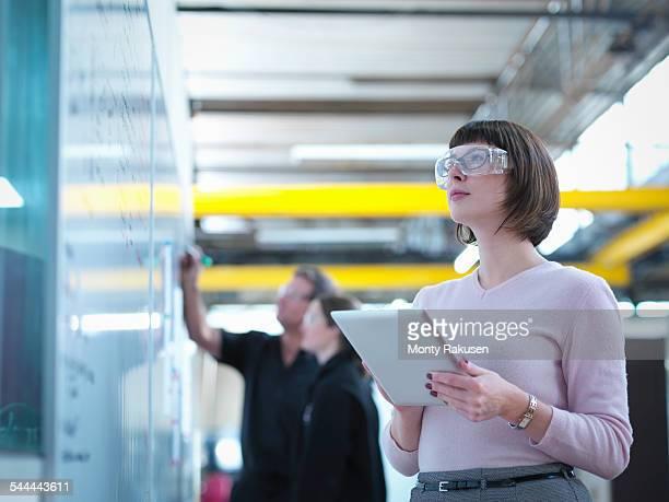 Female worker using digital tablet in factory