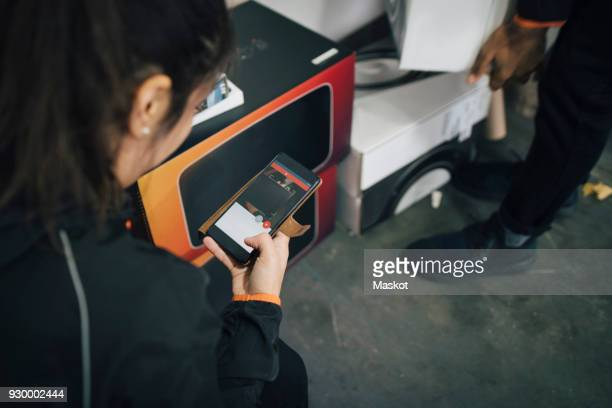 Female worker using mobile phone during delivery with coworker