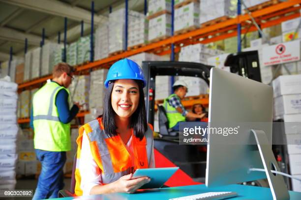 Female Worker Using Tablet Computer In Distribution Warehouse
