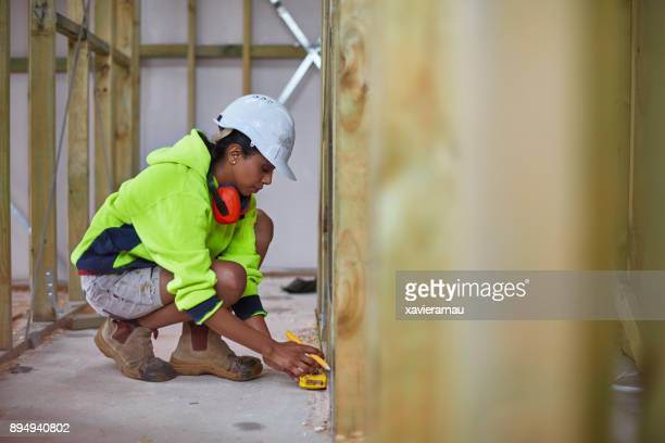 Female worker using tape measure at site