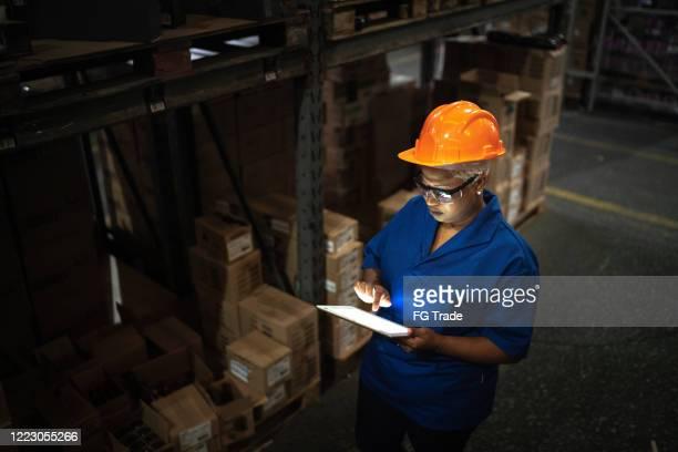 arbeiterin zu fuß und mit digitalen tablet im lager - überstunden machen stock-fotos und bilder