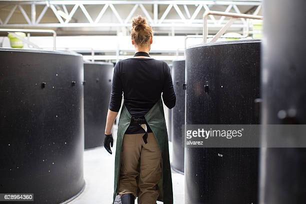 Female worker walking through storage tanks in fish farm