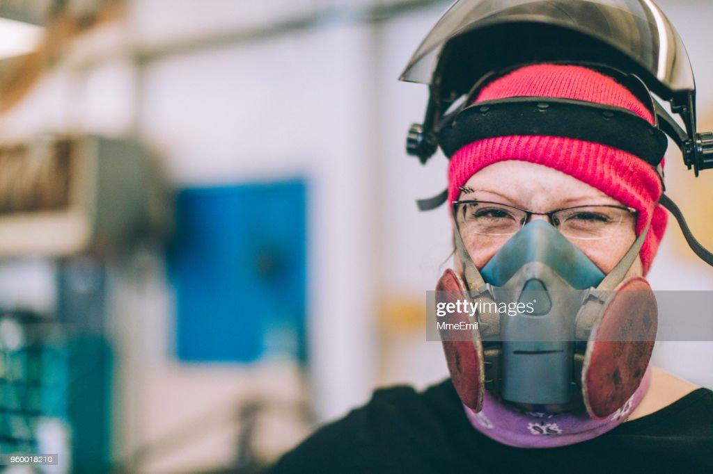 Arbeitnehmerin trug eine Maske und Helm. Lächelnd in die Kamera : Stock-Foto