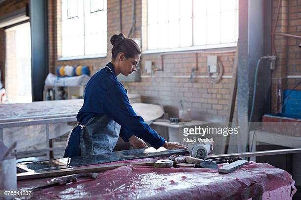 Female worker wiping marble slab at factory