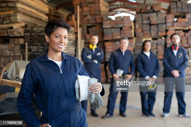 female worker with a group at a wood factory - labor union stock pictures, royalty-free photos & images