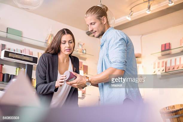 Female worker with colleague discussing while holding product in candy store