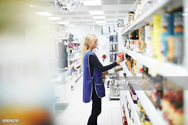 female worker working at convenience store - convenience store stock photos and pictures