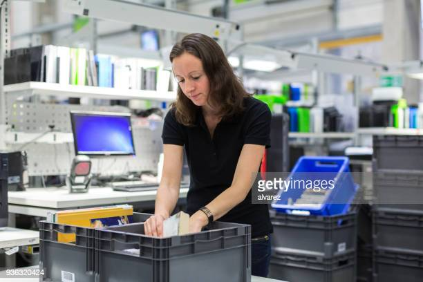 female worker working in distribution warehouse - industrial storage bins stock pictures, royalty-free photos & images