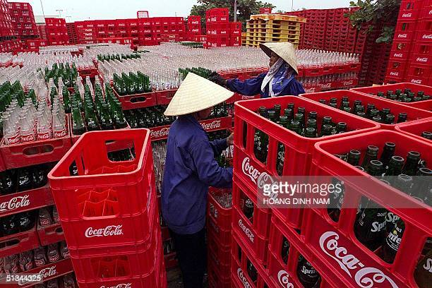 Female workers arrange empty bottle boxes at a CocaCola factory at Ngoc Hoi in the northern Vietnamese province of Ha Tay 13 July 2000 The United...