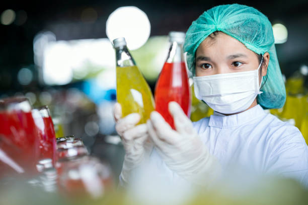 Female Workers checking glass bottle of the Basil seed mixed pineapple and lychee fruit drink product. Food and Beverage Industry