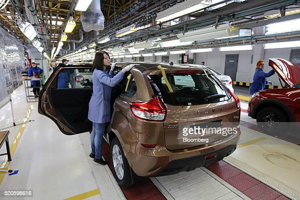 Female workers conduct quality control checks on Lada XRay automobiles at the end of the production line at the headquarters of AvtoVAZ OAO in...