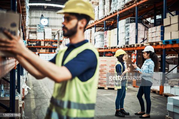 female workers discussing with male in foreground - arranging stock pictures, royalty-free photos & images