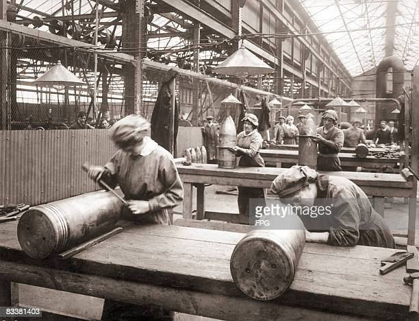 Female workers inspect 92inch HE shells in the bond room of an English munitions factory during World War I circa 1915